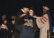 A woman accepting her diploma at a graduation ceremony